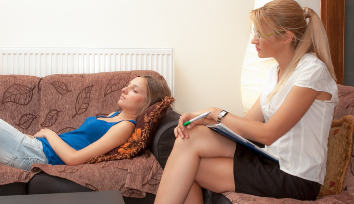 hypnosis session - woman is laying on couch with therapist in a chair