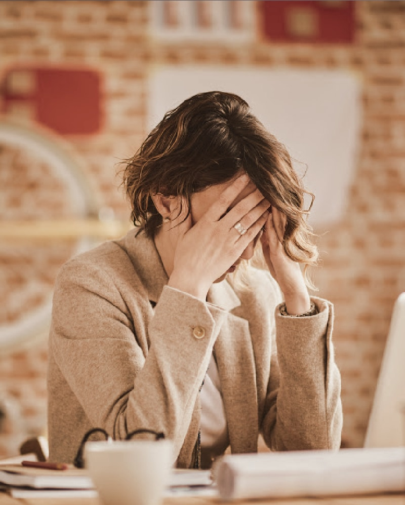 lady sitting at laptop with head in hands sad about her website