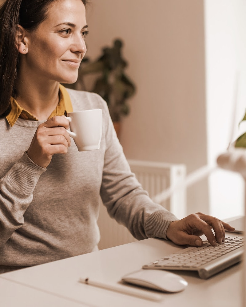 woman with coffee doing monthly updates on her website